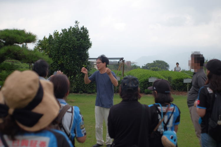 The manager of the tea facility explaining to the guests how to pick green tea leaves(茶葉の摘み方を教える)